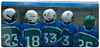 Lineup of kids playing hockey sitting on the bench